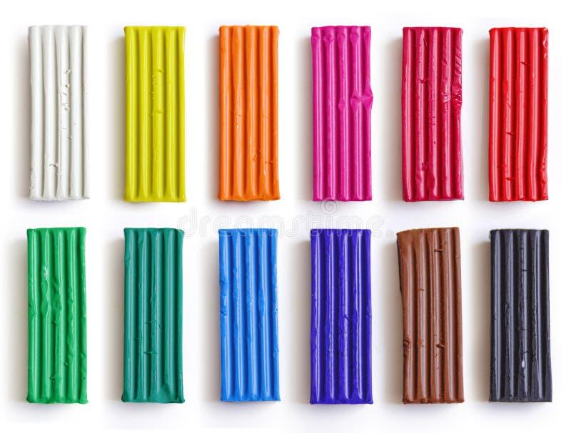 Uppsättning av färgrika plasticinepinnar som isoleras på vit bakgrund Regnbåge som modellerar lerastycket för barnlek och kreativ fotografering för bildbyråer