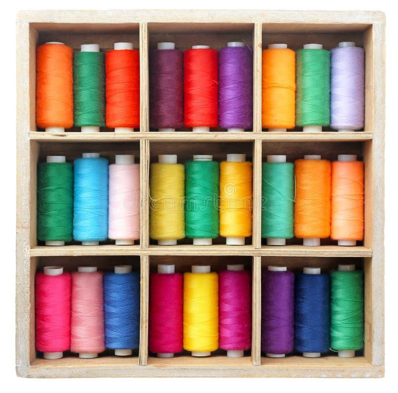 Uppsättning av färgsömnadtrådar i trä arkivfoton
