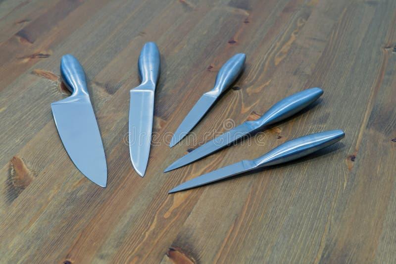 Uppsättning av fem stålkökknivar på trätabellen arkivbilder