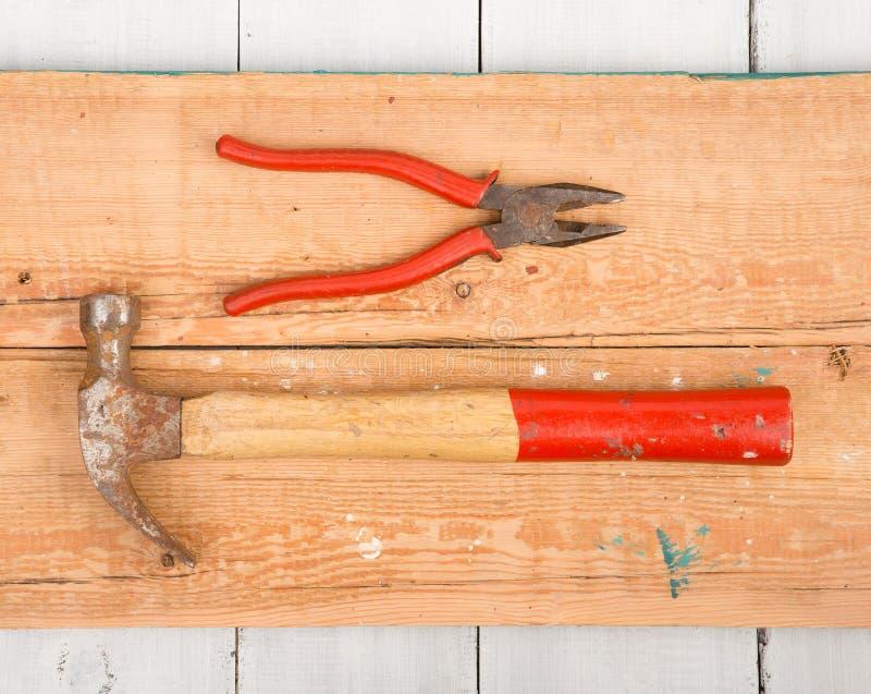 Uppsättning av gamla hjälpmedel hammare och plattång på träbakgrund royaltyfria bilder