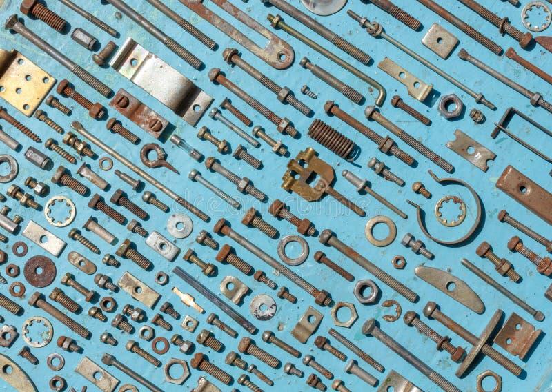Uppsättning av gamla rostiga metallskruvar, muttrar - och - bultar på en blå bakgrund royaltyfri bild