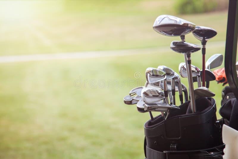 Uppsättning av golfklubbar över grön fältbakgrund royaltyfri fotografi