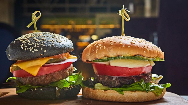 Uppsättning av hemlagade hamburgare i svartvita bullar med tomaten, grönsallat, ost, lök på det wood portionbrädet över mörker royaltyfria bilder