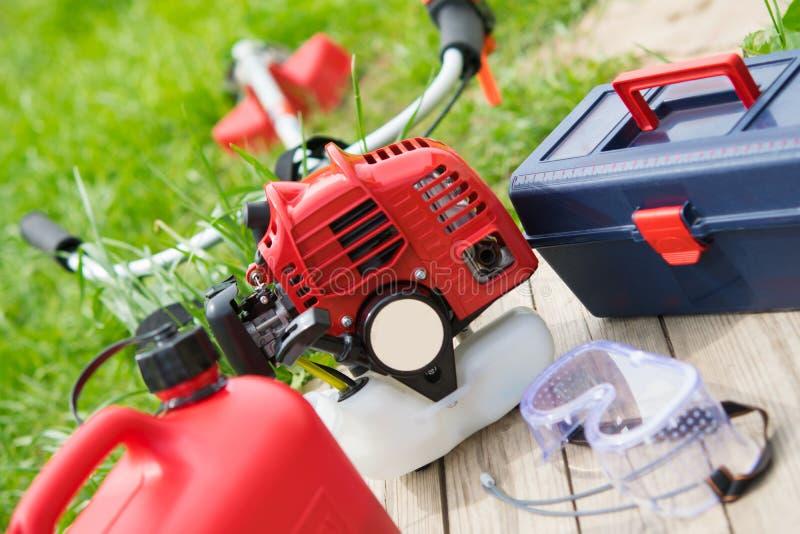 Uppsättning av hjälpmedel för omsorgen av grön gräsmatta, röd chainsaw, bränslecans, ett hjälpmedel för justering fotografering för bildbyråer