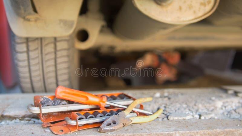 Uppsättning av hjälpmedel framme av mekanikern under skruvande detaljer för en bil på under magasinet fotografering för bildbyråer