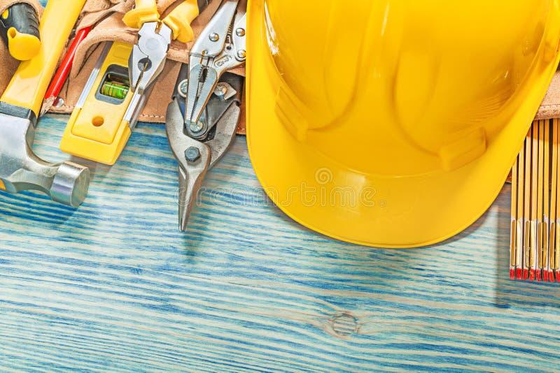 Uppsättning av konstruktionshjälpmedel i läderbyggnadsbälte på träboa fotografering för bildbyråer