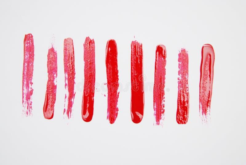 Uppsättning av kosmetiska texturborsteslaglängder som isoleras på vit måla röd textur colors smink arkivbild