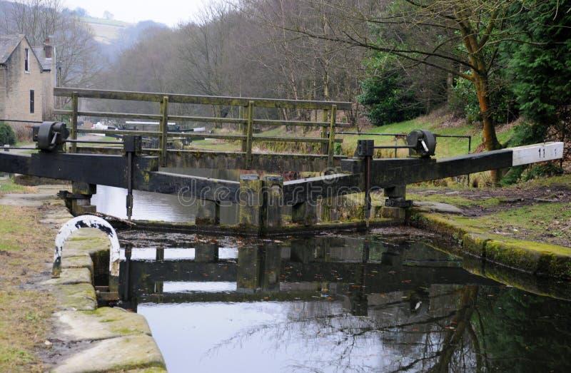 Uppsättning av låsportar på en kanal med träspången royaltyfri foto