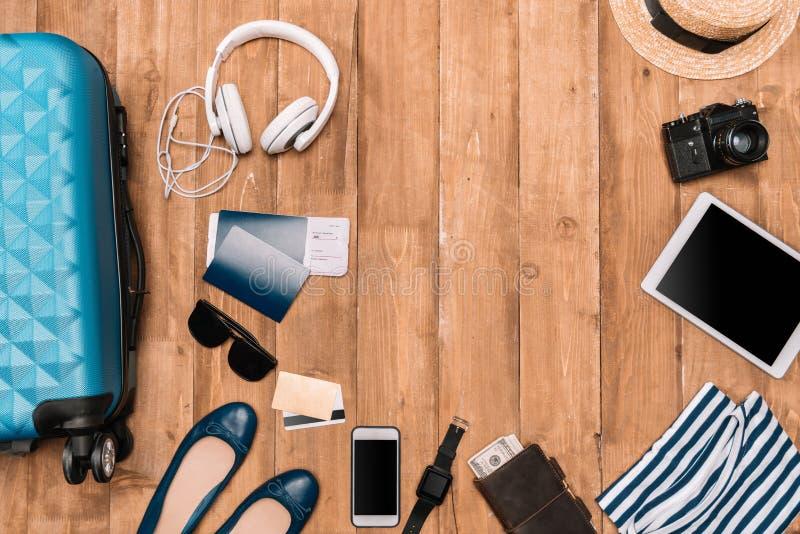 Uppsättning av lopptillbehören på trägolv Lägenheten lägger med bagage, pass, digitala grejer och kläder arkivfoto