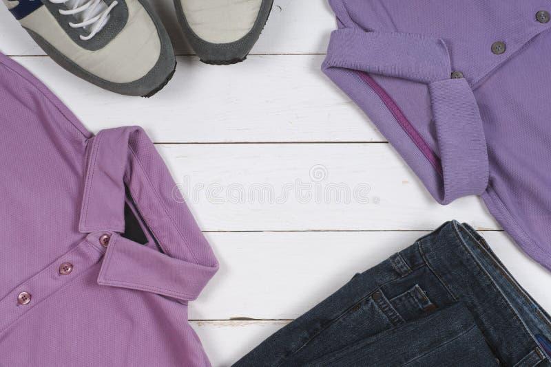Uppsättning av mäns kläder och skor på träbakgrund Sportar T-tröja och gymnastikskor i ljusa färger Top beskådar royaltyfri fotografi