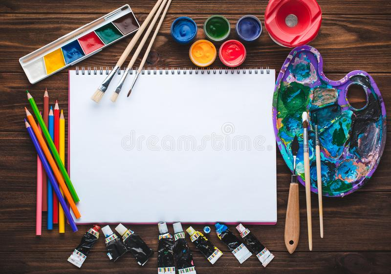 Uppsättning av målarfärger, blyertspennor, hjälpmedel för att måla och tom vitbok arkivfoto