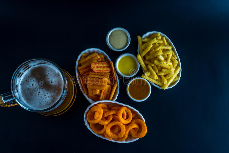 Uppsättning av mellanmål med doppet och halv liter av öl, frasiga mellanmål, goda fo royaltyfria bilder