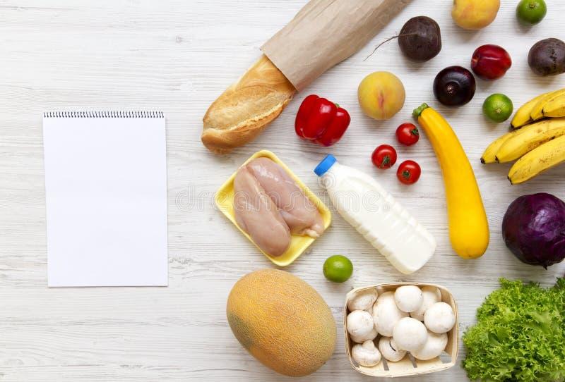 Uppsättning av ny sund mat för variation med papper för anmärkningar på vit träbackfround, sikt från över Livsmedelsbutikplanbegr royaltyfri bild