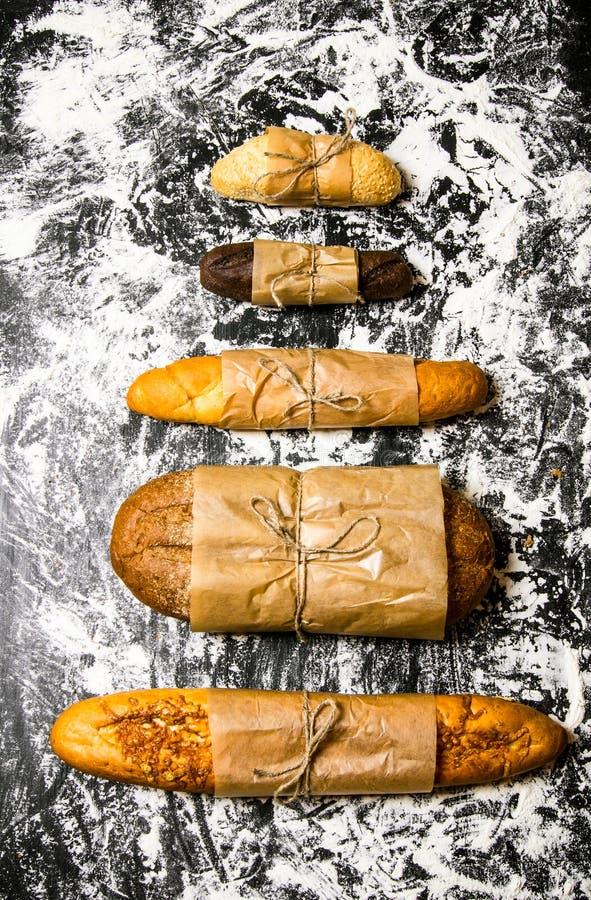 Uppsättning av nytt bröd som slås in i papper arkivfoton