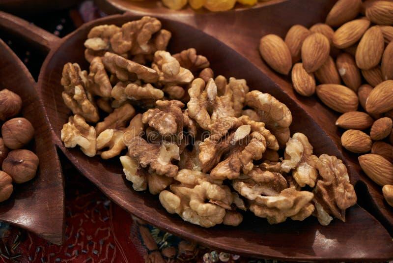 Uppsättning av olika muttrar, mandlar, valnötter, hasselnötter i brun träbunke royaltyfri fotografi