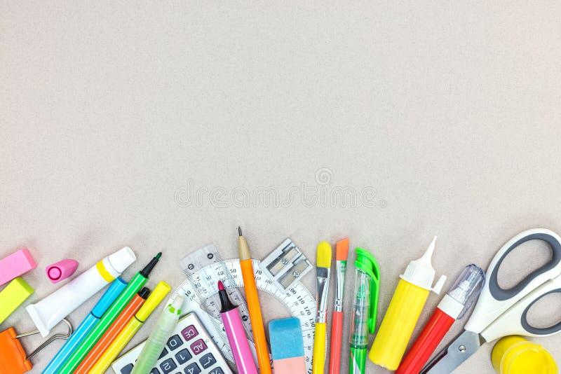 Uppsättning av olika skolatillförsel för ungar på grå skrivbordyttersida arkivfoto