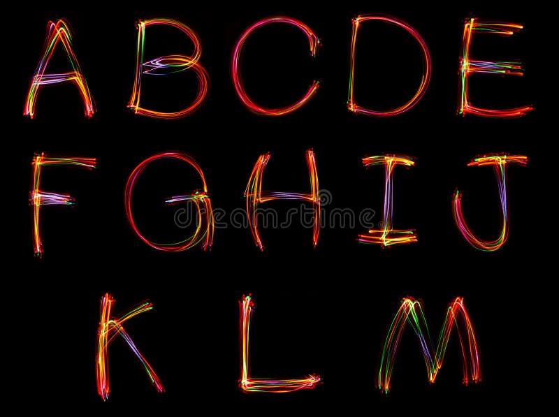 Uppsättning av ordhandstil från ljus på den svarta bakgrunden arkivbilder