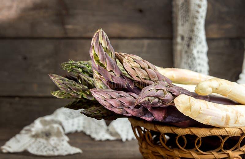 Uppsättning av rå vit, gräsplan, purpurfärgad sparris på gammalt trälantligt royaltyfria foton