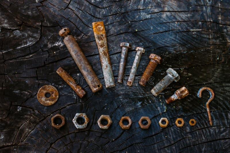 Uppsättning av rostiga tokiga och små hjälpmedel för skruvar, på en mörk träbakgrund arkivfoto