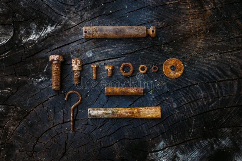 Uppsättning av rostiga tokiga och små hjälpmedel för skruvar, på en mörk träbakgrund royaltyfri fotografi