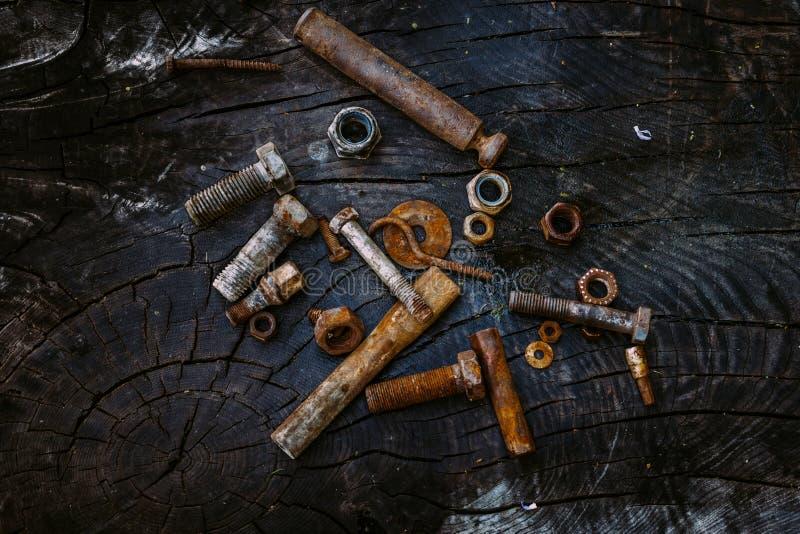 Uppsättning av rostiga tokiga och små hjälpmedel för skruvar, på en mörk träbakgrund royaltyfria bilder