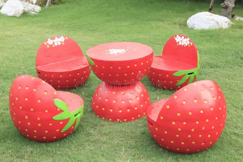 Uppsättning av skrivbordet för uteplats för röd jordgubbeträdgård det utomhus- på grönt gräs f fotografering för bildbyråer