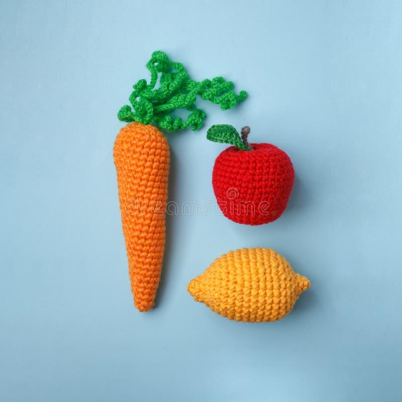 Uppsättning av stack leksaker citron, morot, äpple på blå bakgrund Tidigare känsel- utveckling av barn, hantverkleksaker, vegetar royaltyfria bilder