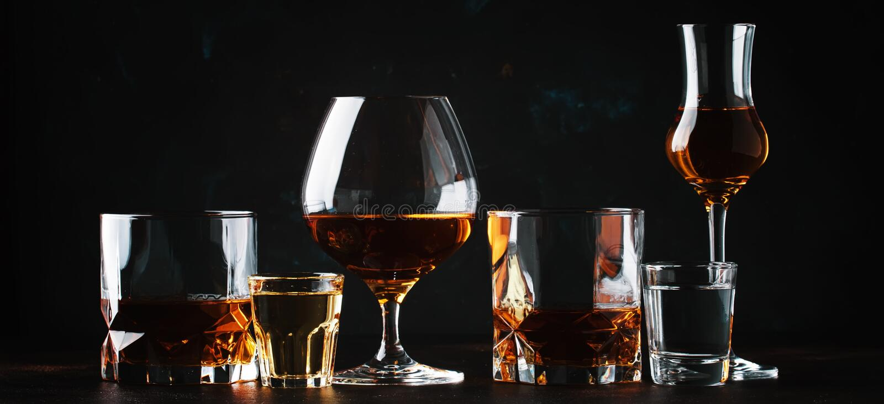 Uppsättning av starka alkoholdrycker i exponeringsglas och skottexponeringsglas i asso arkivfoto