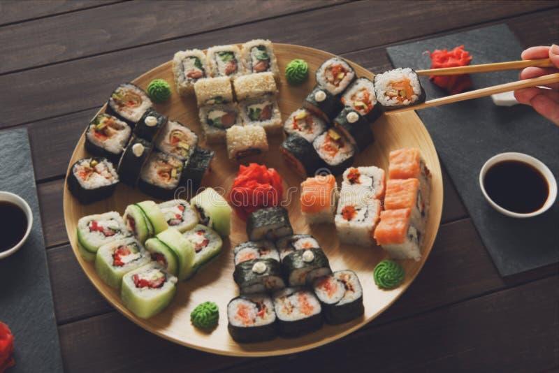 Uppsättning av sushimaki och rullar på svart lantligt trä royaltyfri bild