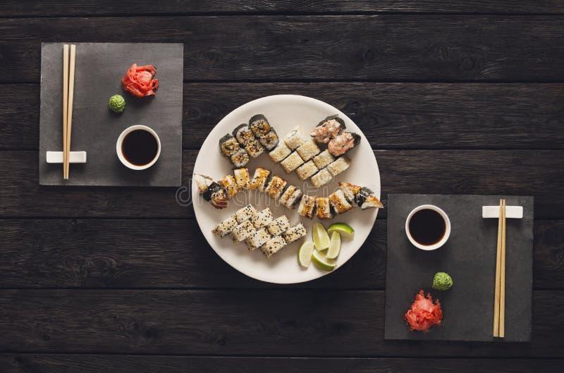 Uppsättning av sushimakien och rullar på svart lantligt trä, bästa sikt royaltyfria bilder