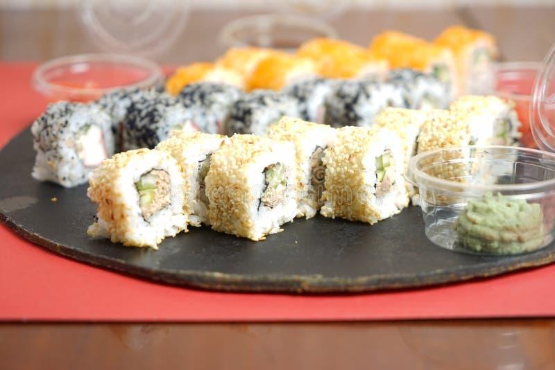 Uppsättning av traditionell japansk mat på en mörk bakgrund Sushirullar, nigiri, rå laxbiff, ris, gräddost arkivbild