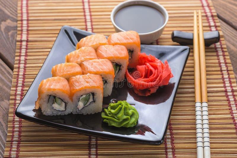Uppsättning av uppsättningen för Philadelphia sushirulle på den keramiska plattan med wasabi, ingefäran, soya och pinnar arkivbilder
