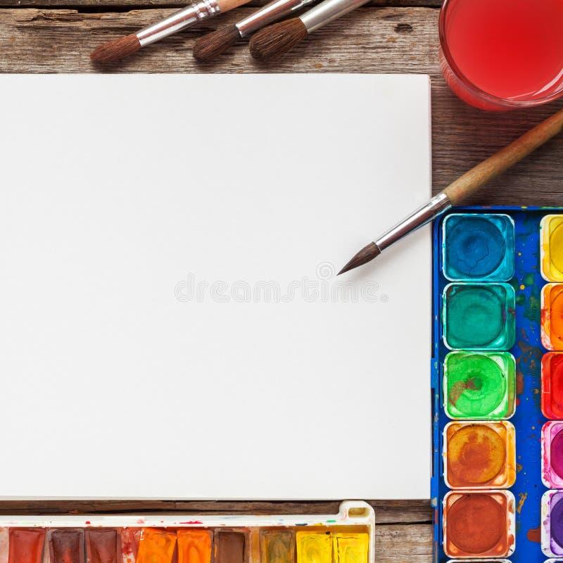 Uppsättning av vattenfärgmålarfärger, borstar för att måla och tomt papper fotografering för bildbyråer