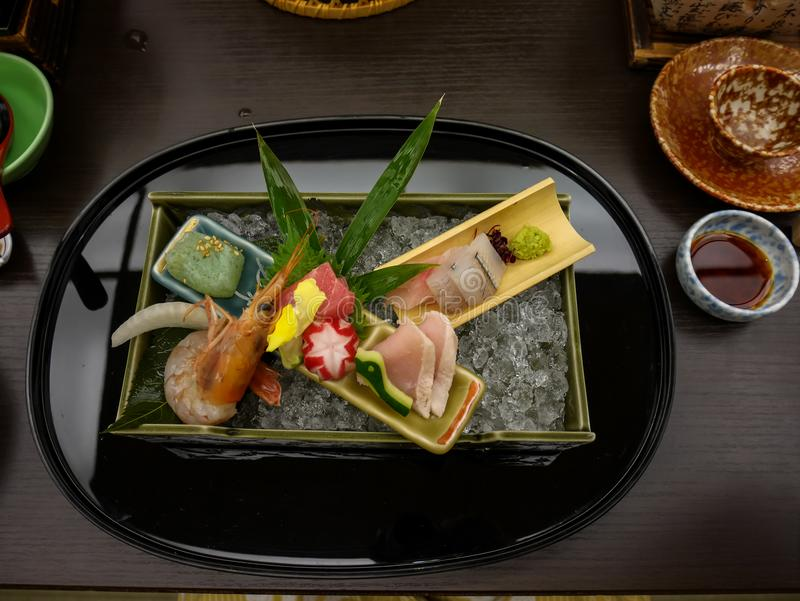 Uppsättning för sashimi för japansk ryokan kaisekimatställe dekorativ inklusive Stillahavs- blå fenatonfisk, räka, större amberja fotografering för bildbyråer