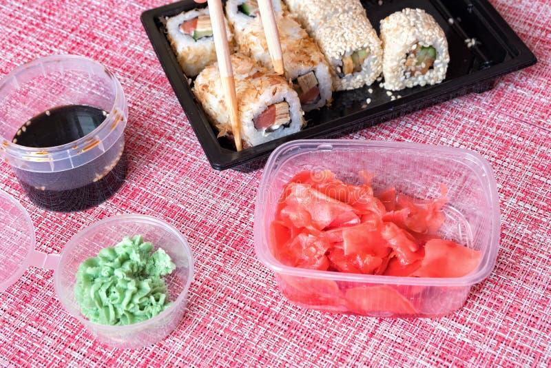Uppsättning för sushirulle, soya, wasabi, inlagd ingefära, pinnar i en disponibel behållare på en servett arkivbilder