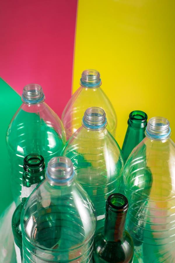 Uppsättningar av tomma glasflaskor och plast- flaskor med ingen etikett på en livlig gräsplan, röd för vin och gul kulör bakgrund arkivbilder