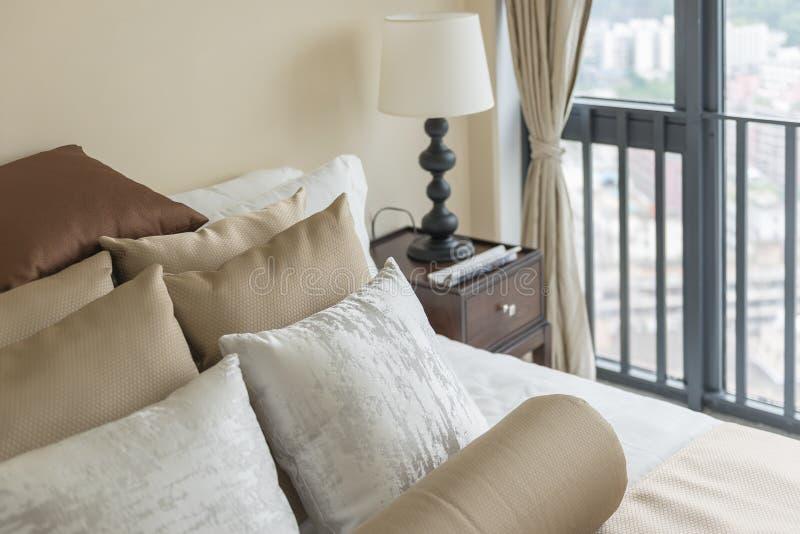 uppsättningen av brunt kudde på säng i klassiskt sovrum arkivbild