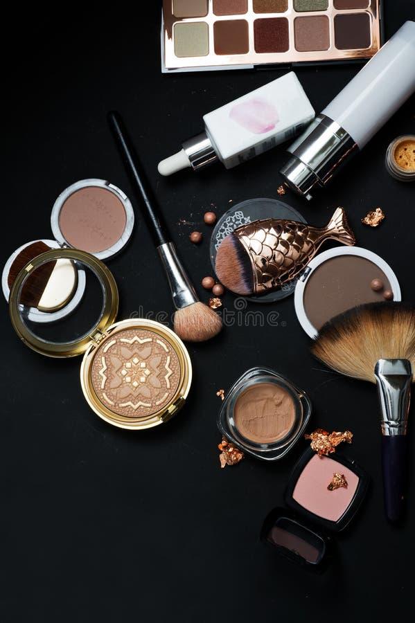 Uppsättningen av dekorativa skönhetsmedel med makeup borstar på svart backgro royaltyfri bild