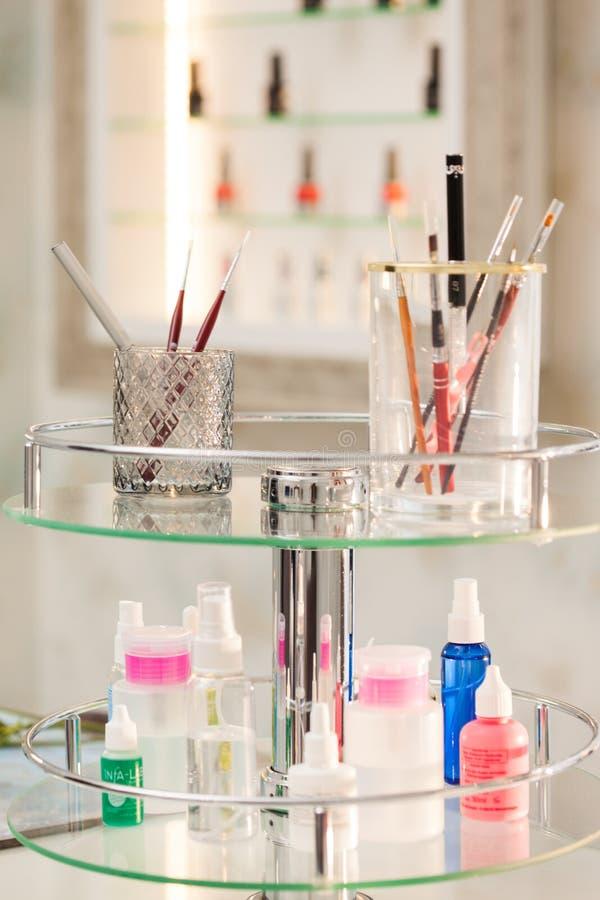 Uppsättningen av det yrkesmässiga sminket borstar och hjälpmedel för manikyr i glass behållare på den glass tabellen i skönhetsal arkivbilder