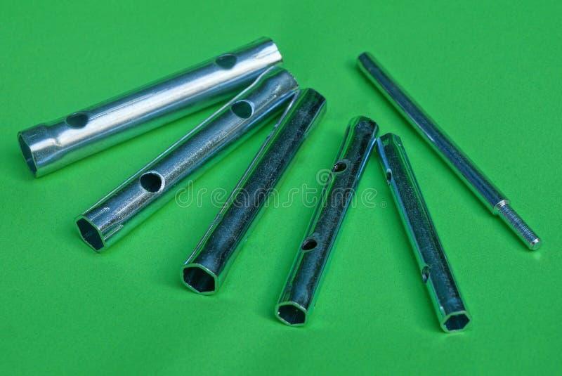 Uppsättningen av grå färger belägger med metall tubformiga sluttangenter på en grön tabell royaltyfri bild