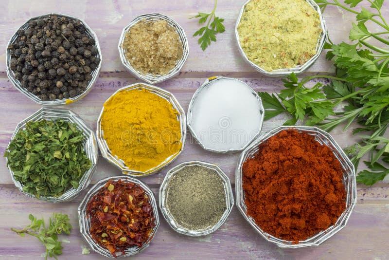 Uppsättningen av olika kryddor i skinande bunkar på en lila färgade trä royaltyfria bilder