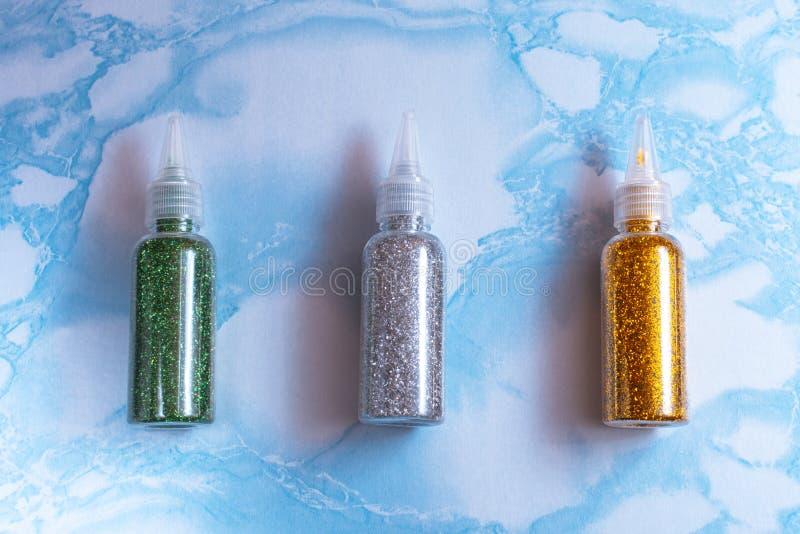 Uppsättningen av smaragd, silver och guld blänker i plast- flaskor för tvål som gör på yttersidan av blå marmor, tätt upp som är  royaltyfri fotografi