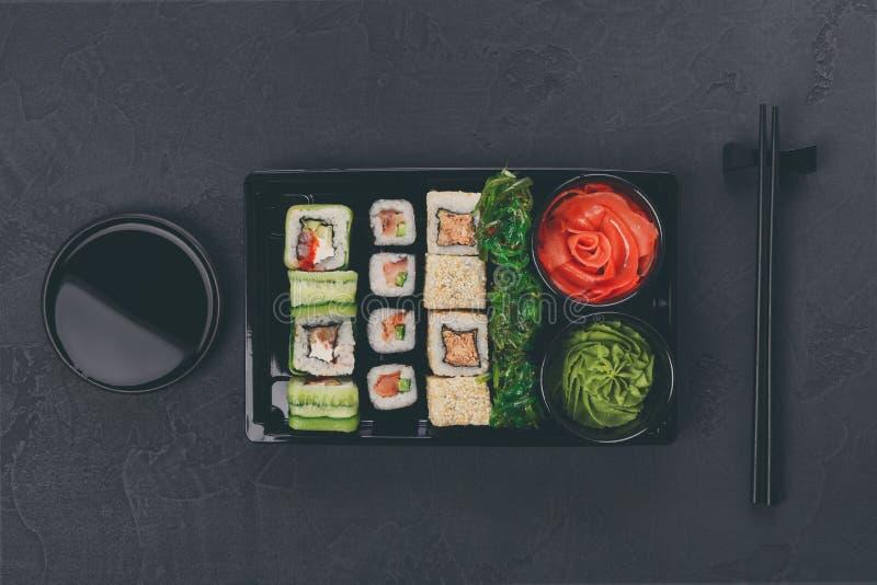 Uppsättningen av sushimaki och rullcloseupen i leverans boxas fotografering för bildbyråer
