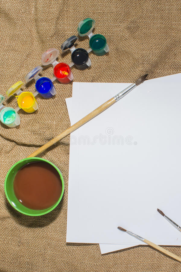 Uppsättningen av vattenfärgen målar, borstar för att måla och tomt vitbokark av sketchbooken arkivfoton