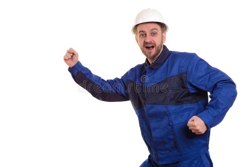Uppsöka manbyggmästaren i körningar för den hårda hatten och overallför konstruktion på den vita bakgrunden royaltyfria foton