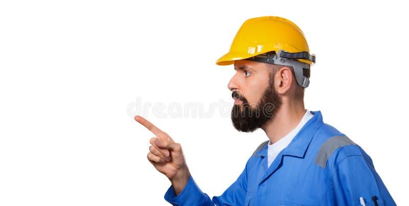 Uppsökt byggmästare i den hårda hatten, ordföranden eller repairmanen i den gula hjälmen som pekar hans finger i byggmästare för  fotografering för bildbyråer