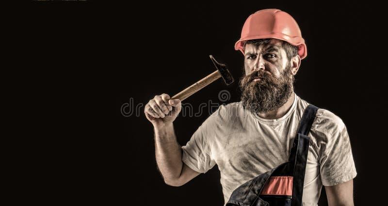 Uppsökt byggmästare som isoleras på svart bakgrund Sk?ggig manarbetare med sk?gget, byggnadshj?lm, h?rd hatt Bulta f?r hammare arkivbilder