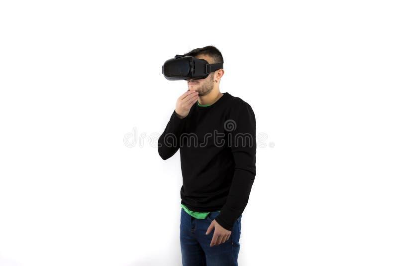 Uppsökt fundersam och förvirrad ungt trevligt och modernt med vrexponeringsglas som tycker om virtuell verklighet arkivbild
