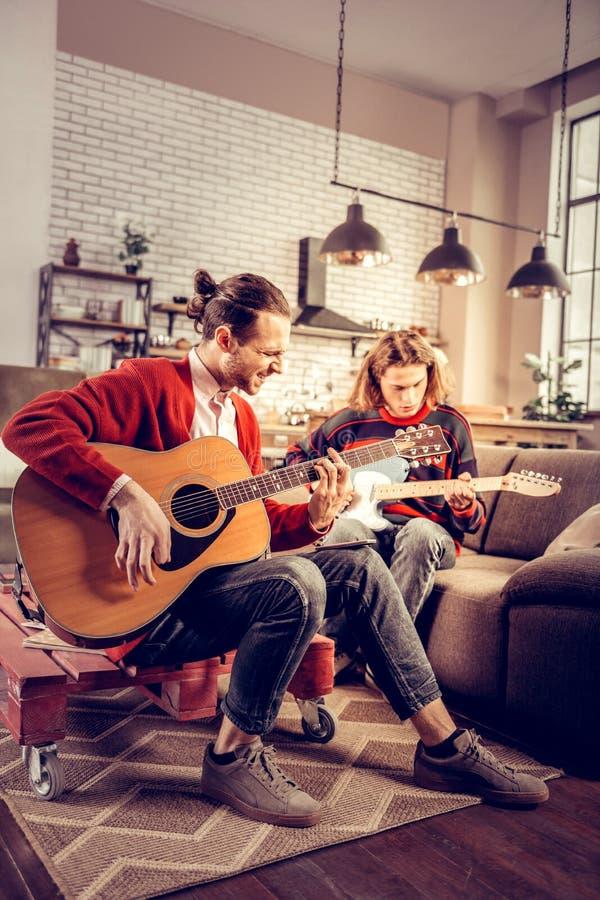 Uppsökt gitarristkänsla som tillfredsställs, når att ha komponerat melodi royaltyfri bild