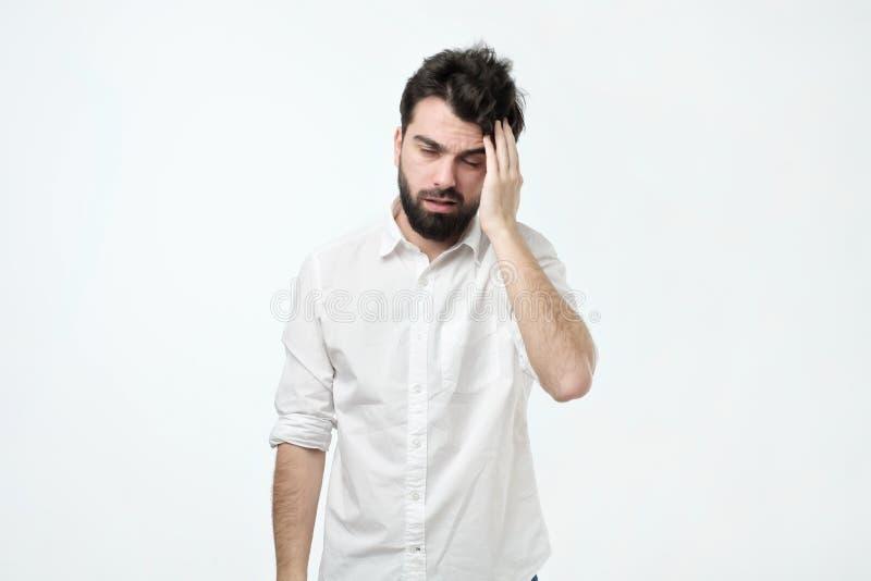 Uppsökt man med det smutsiga hår och skägget, gnuggbildhuvud och tröttas eller ha bakrus arkivfoto